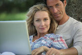 Couple sat in the park with laptop — Stock Photo