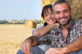 Farming couple sat by hay — Stock Photo