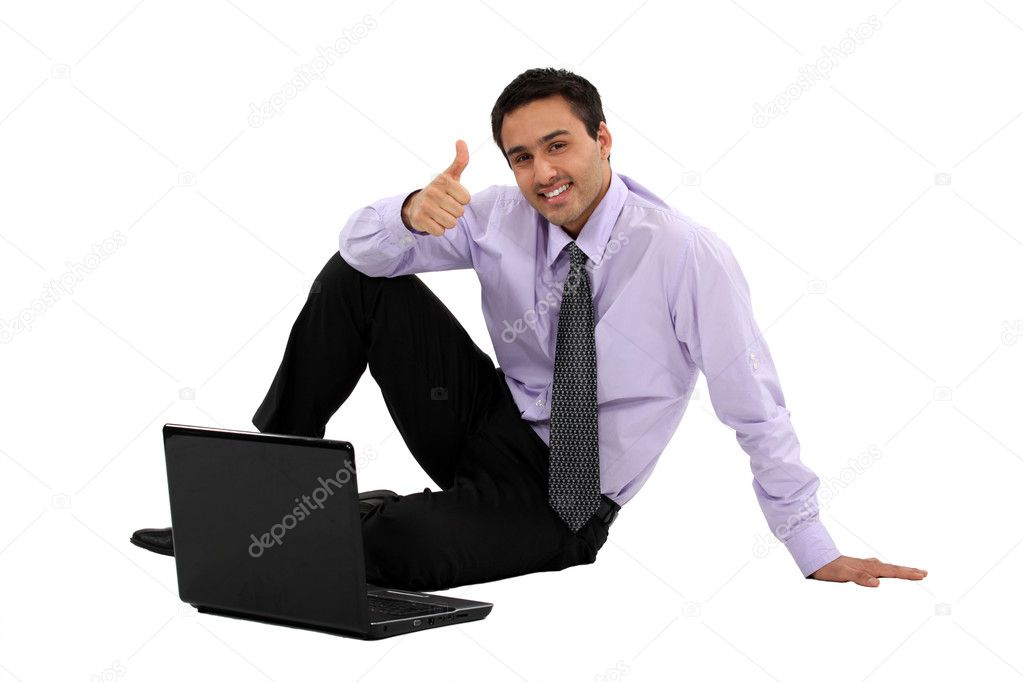 Businessman sitting on the floor with his laptop and making a thumbs up sign  Stock Photo #8164885