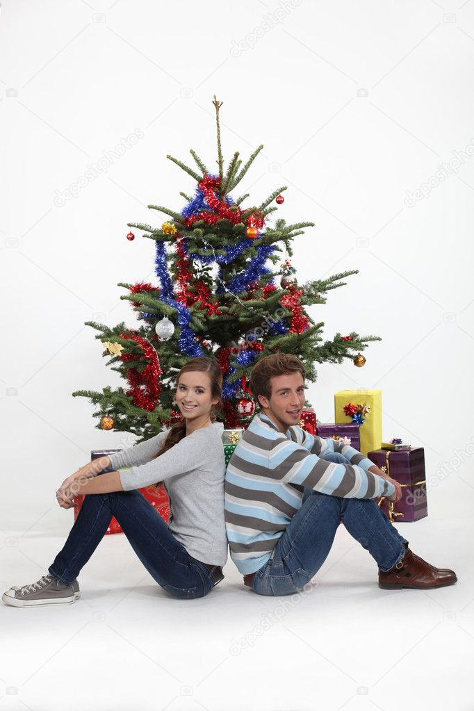 Couple sitting in front of their Christmas tree  Stock Photo #8166876