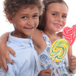 Stock Photo: Two friendly kids eating colorful lollipops