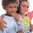 Two friendly kids eating colorful lollipops — Stock Photo
