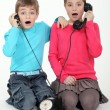 Shocked children using telephone — Zdjęcie stockowe #8170094