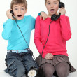 图库照片: Shocked children using telephone