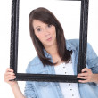 Brunette holding empty picture frame — Stock Photo