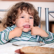 Toddler pulling a face at the table - Stock Photo