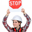 Female builder holding stop sign - Stock Photo