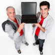Two men showing a laptop computer — Stockfoto