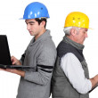 Builder and apprentice with laptop and clipboard — Stock Photo