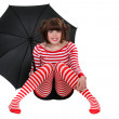Woman in striped clothes holding an umbrella — Stock Photo