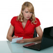Pensive blond woman taking notes from laptop screen — Stock Photo