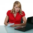 Pensive blond woman taking notes from laptop screen — Stock Photo #8175623