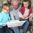 Couple looking at a laptop with their grandchildren — Stock Photo #8176642