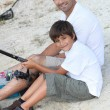 Father and son at fishing party - Stock Photo