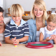 Young family playing dice — Stock Photo #8176889