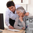 Young man showing grandmother computer — Stock Photo