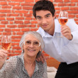 Senior lady and young man making a toast — Stock Photo