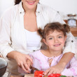 Stock Photo: Mother and daughter cooking together.