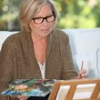 Grandmother painting — Stock Photo