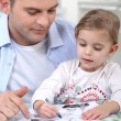 Little girl colouring under dad's watchful eye — Stockfoto #8177195