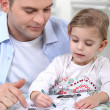 Stock Photo: Little girl colouring under dad's watchful eye