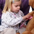 A little girl playing doctor with her teddy bear. — Stock Photo