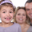 A cute little girl with her parents in the background. — Stock Photo