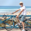 Man with a bike at the beach - Stock Photo