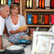 Couple looking at local pottery on holiday - Stock Photo
