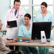 Doctor, patient, and medical secretaries at reception — Stock Photo #8179220