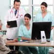 Doctor, patient, and medical secretaries at reception — Stock Photo