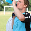 Stock Photo: Football player drinking energy drink