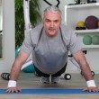 Mature man doing pushups - Stock Photo
