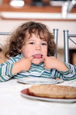 Toddler pulling a face at the table — Stock Photo