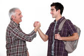 Mature man and young man handshaking — Stock Photo