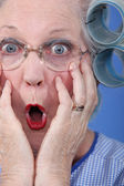 Shocked old lady wearing hair rollers — Stock Photo