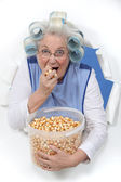 Elderly lady eating popcorn — Stock Photo