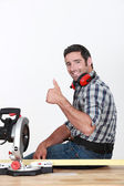 Approving tradesman using a mitre saw — Stock Photo