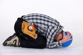 Construction worker curled up — Stock Photo