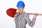 Woman resting shovel across shoulder — Stock Photo