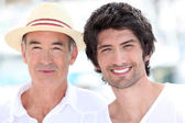 65 years old man wearing a straw hat and a 25 years old man posing in a sum — Stok fotoğraf