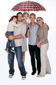 Family standing under umbrella — Stock Photo