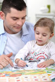 Little girl colouring under dad's watchful eye — Stock Photo