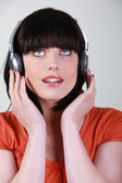 Woman listening to music against studio background — Stock Photo