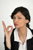 Brunette businesswoman giving OK sign — Stock Photo