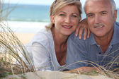 Middle aged couple lying in the sand dunes — Stock Photo