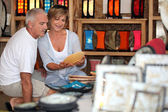 Couple looking at local pottery on holiday — Stock Photo