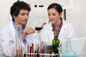 Man and woman testing wine in laboratory — Stock Photo