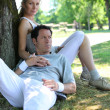 Portrait of sporty couple relaxing by tree - Stockfoto