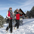 Couple trekking through snow — Stock Photo